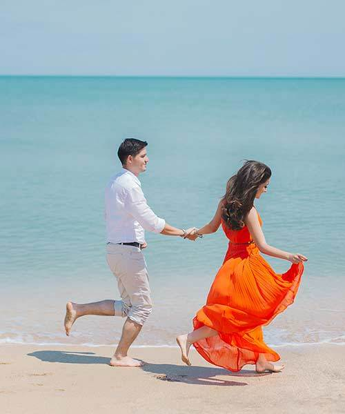 couple holding hand running on the beach cheap date